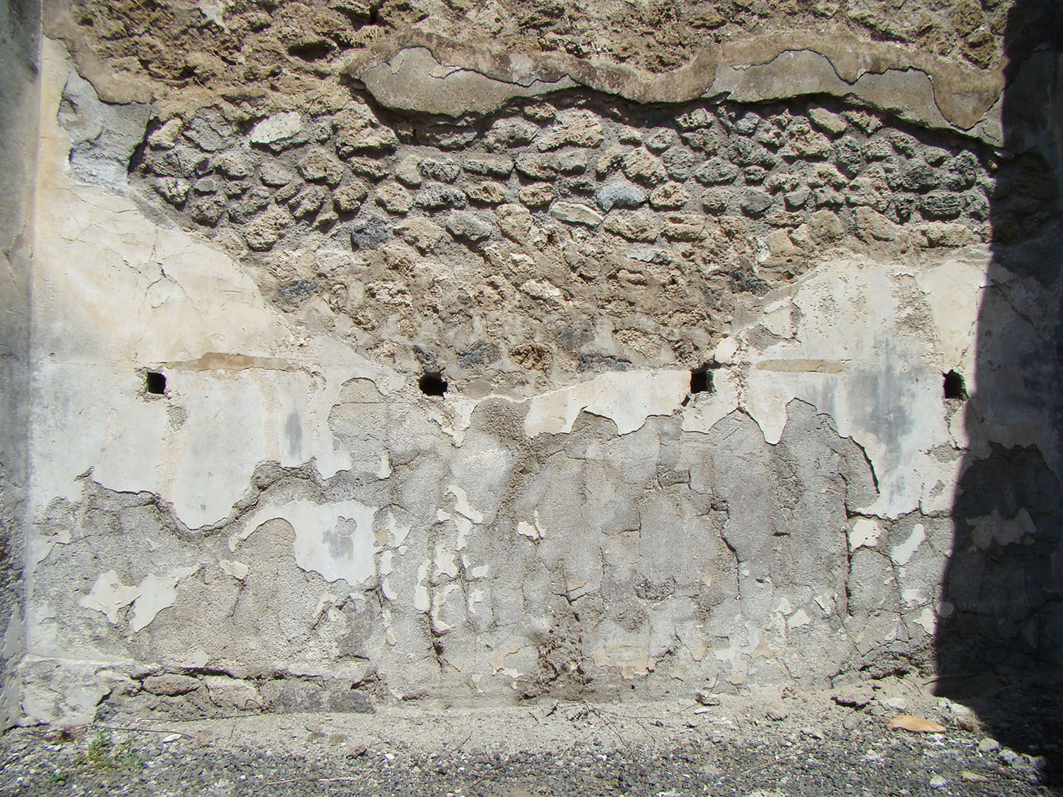 Fig. 8. House VI.13.13, Pompeii, right ala, detail of back wall with holes for shelves (the top row has been concealed by modern restoration).