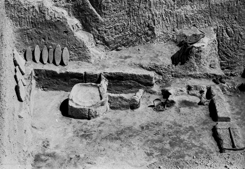Fig. 4. The Bakery in Southwest House, facing north with the grindstones displayed against the scarp. From west to east are the kneading trough, storage bin, and two ovens (courtesy Penn Museum, Gordion Project Archives, image no. GR 66-10).