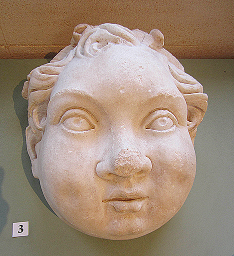 Fig. 4. Protome of a putto wearing an ivy wreath (the infant Dionysus?), ht. 29 cm, Chiragan. Toulouse, Musée Saint-Raymond, inv. no. Ra 37a.