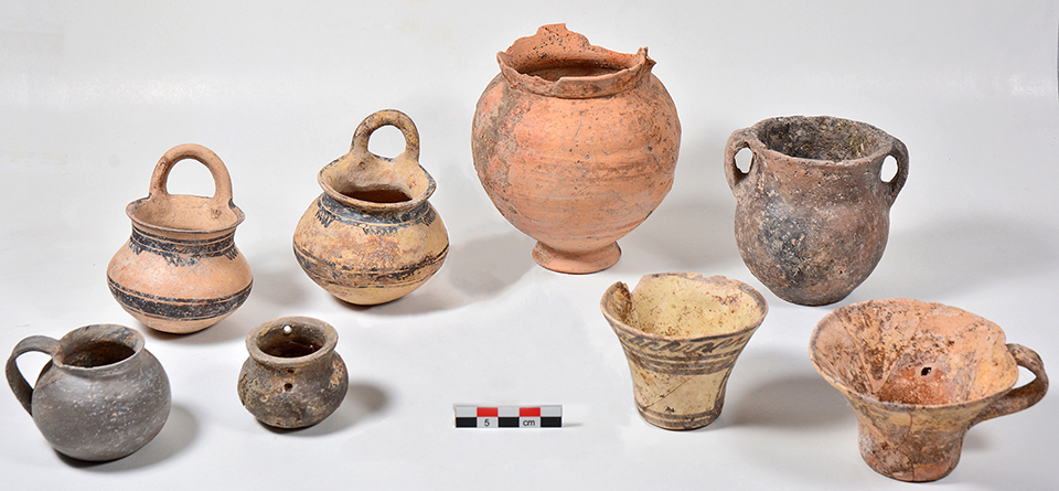 Fig. 6. Ceramic vessels from Tomb 11 outside the southeast corner of the Blue Stone Structure; front row, left to right: Gray Minyan squat juglet (P1921), Gray Minyan pyxis (P1916), two matte-painted Vapheio cups (P1917, P1922); back row, left to right: two matte-painted vertical ring-handled cups (P1851, P1908), bichrome jug (P1915), amphoriskos (P1920).