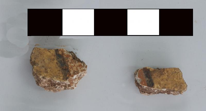Fig. 8. Fragments (3055–16b, 3055–16d) of painted wall fresco, with red, orange (or yellow), and black decoration, from area D-South.