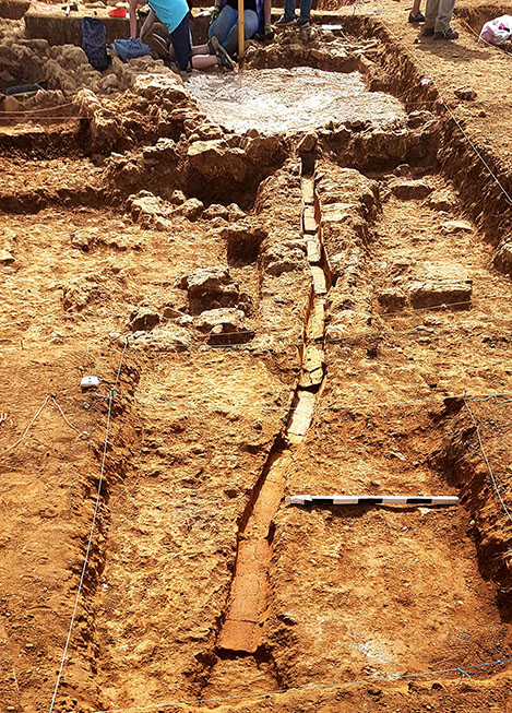 Fig. 13. Phase 4 plaster floor with clay channel west of Unit E. View from the west.