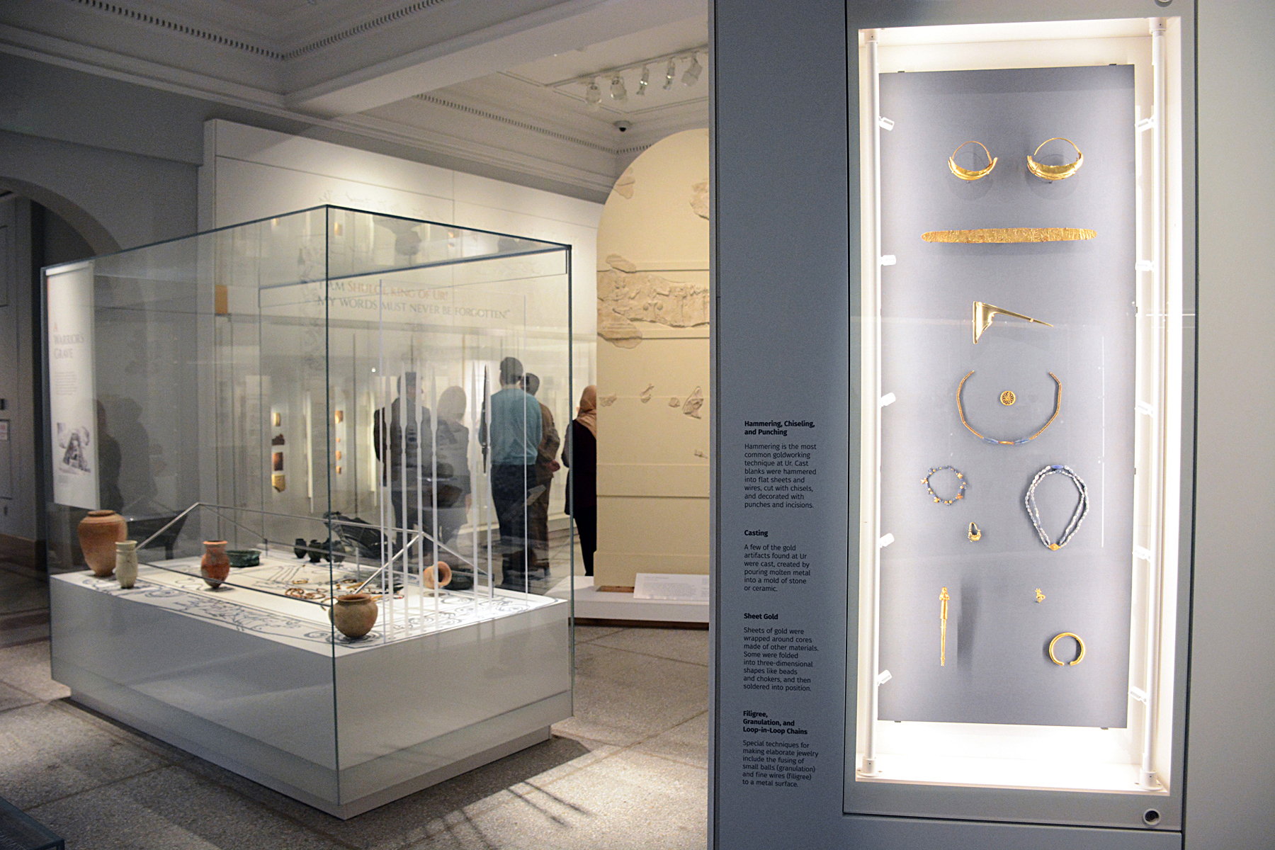 Fig. 2. A view in the Penn Museum's Middle East Galleries. On the right, finely crafted jewelry made of gold and precious stones, excavated from the royal tombs at Ur. The central case features materials from the excavation of a warrior's grave, dating to ca. 100 years after the royal tombs at Ur, likely the tomb of an important warrior, who was richly adorned and buried along with numerous weapons. In the background is visible the resin-cast reconstruction of Ur-Namma's stele from ca. 2100 B.C.E. (courtesy Penn Museum, Philadelphia).