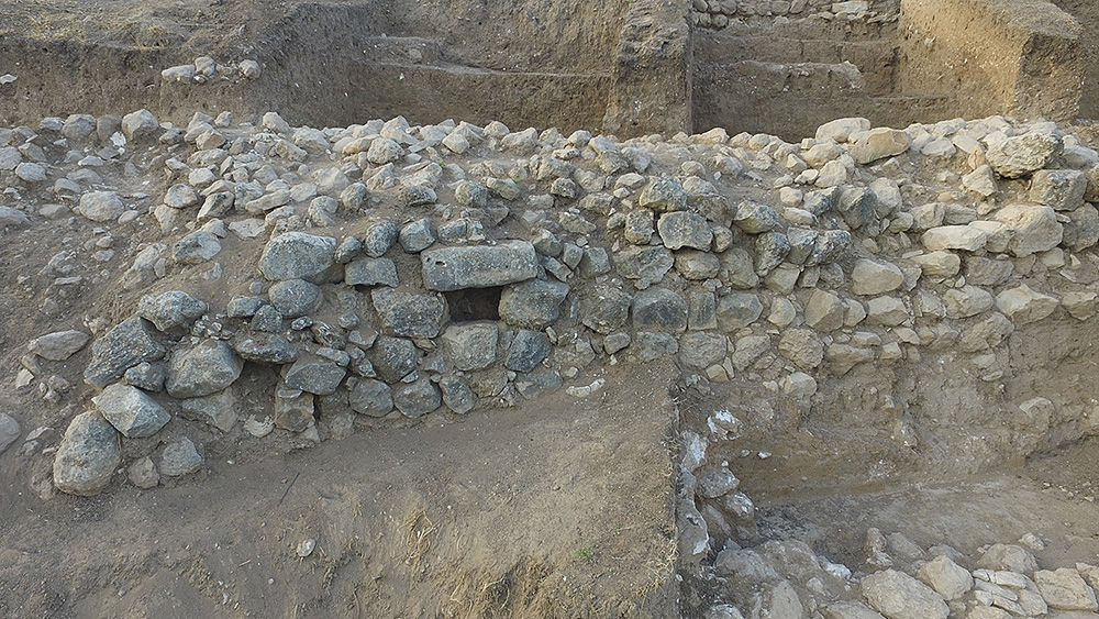 Fig. 11. Close-up high view of the previously unknown city wall of Level V in Area CC, facing south. Note the opening of a drainage system (E. Aladjem, Israel Antiquities Authority).