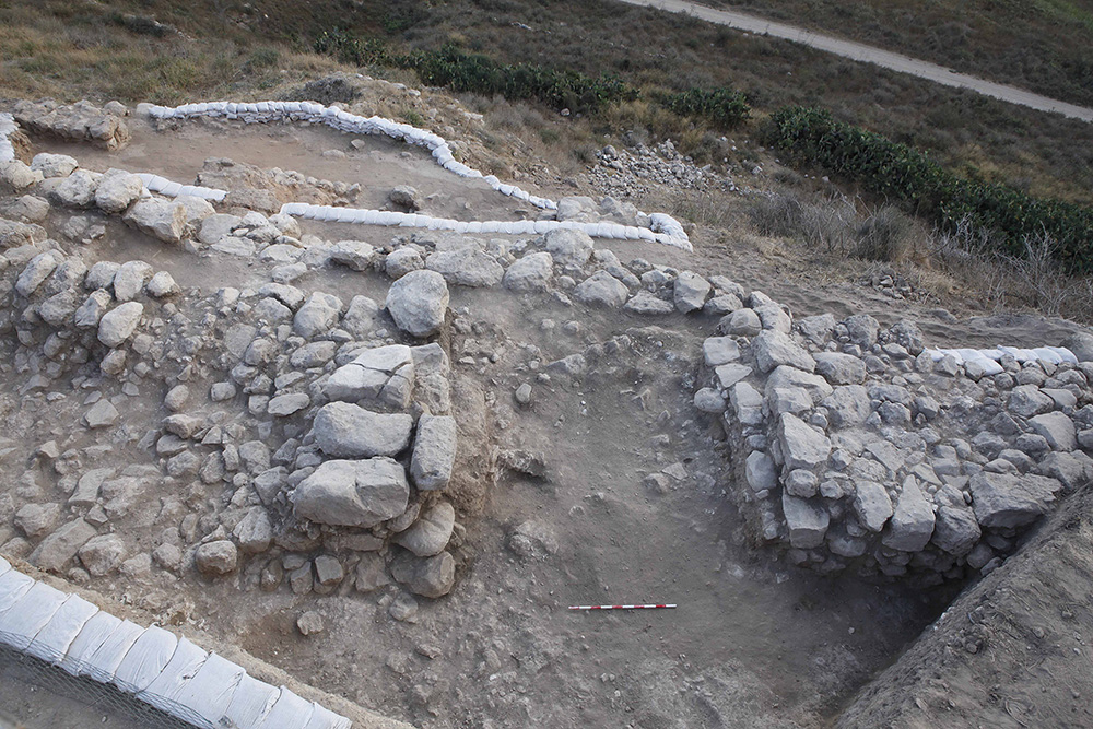 Fig. 18. The Level II city wall and gate leading down to the valley on the eastern slope of Area BB. White sandbags secure the balks.