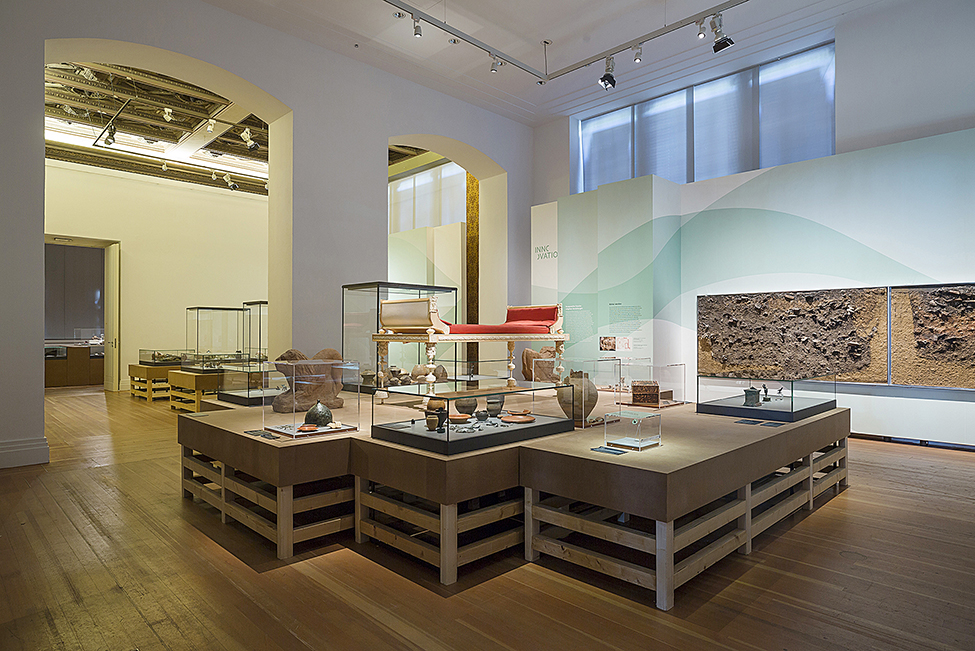 "Fig. 4. View of ""Transfer of Ideas and Spiritual Exchange"" gallery. In the center, reconstruction of a Roman kline from a grave in a cemetery of a legionary camp in Haltern am See, first century C.E. (D. von Becker; © Staatliche Museen zu Berlin, Museum für Vor- und Frühgeschichte)."