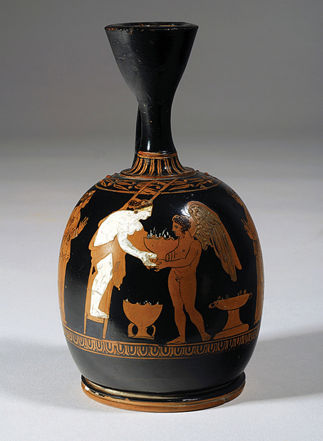 Fig. 3. Athenian red-figure squat lekythos (ca. 390 B.C.E., ht. 14 cm) depicting Eros handing a potted plant to Aphrodite, who is on a ladder. This scene probably alludes to the placement of potted plants on a roof in association with the worship of Adonis. Karlsruhe, Badisches Landesmuseum, inv. no. B39 (courtesy Badisches Landesmuseum).