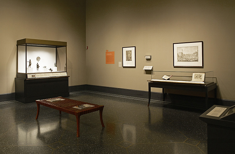 Fig. 3. Installation view of the exhibition's right side: left background, case with Etruscan small bronzes; middleground, bench with catalogues; center background, wall-mounted case with ancient coins; right background, 16th–18th-century illustrated books, an engraving, and a manuscript documenting the Chimaera of Arezzo's western afterlife (E.M. Rosenbery).