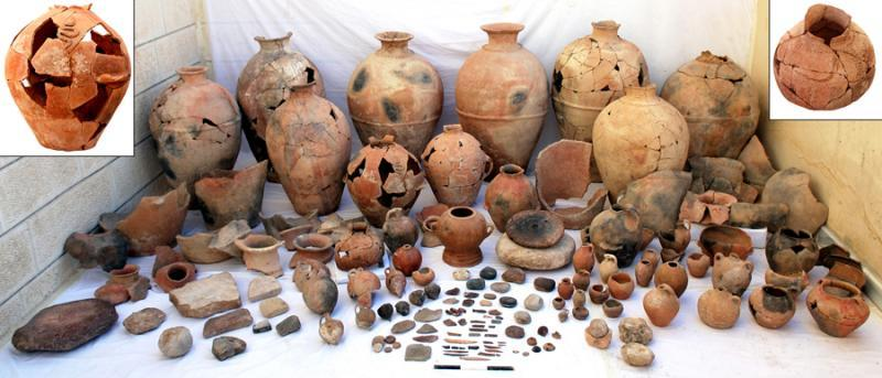 Fig. 27. The assemblage from Pillared Hall (L.1040) in Palace B at Khirbet al-Batrawy (Zarqa), which includes pithoi, red-burnished jugs and pointed juglets, medium-sized jars, ceremonial vessels with applied decorations of snakes and scorpions, and noteworthy objects, among which are a bone knife and several worked bones, pierced seashells, and a carefully worked basalt potter's wheel (L. Nigro).
